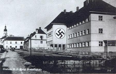 """... a podobný záběr z doby druhé světové války se symbolem nacistické zvůle na tehdy německé """"Horst-Wessel-Schule"""", po němž donedávna svítil na zdi bílý kruh (pohlednice z doby, kdy město patřilo k župě Ober Donau)"""