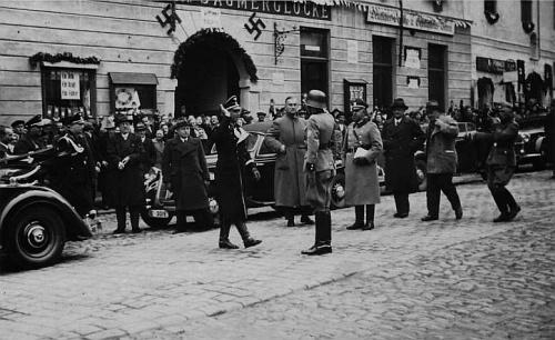 """Osudové scény z roku 1938: před prachatickým hostincem """"Zur Säumerglocke"""" (tj. """"U Soumarského zvonu""""), oněmž je také zmínka v Scheuově textu - v okně vedle vrat lze při větším rozlišení snímku přečíst nápis """"EinReich - Ein Volk -Ein Führer"""""""
