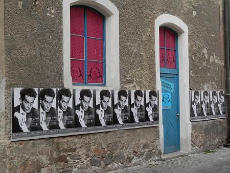 Na plakátě Egon Schiele Art Centrum v Českém Krumlově na českokrumlovské ulici a před budovou Jihočeské vědecké knihovny v Českých Budějovicích