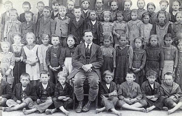 Na snímku ze školního roku 1923/24 v Dolním Markschlagu je pan řídící učitel Schinko dobře obutý zachycen se svými bez výjimky bosými žáky - ten sedící napravo odnohou pana řídícího, Johann Hofer, snímek poslal do krajanského časopisu