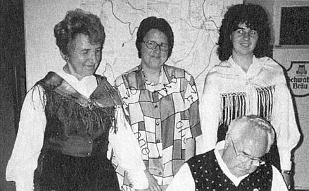 Nad ním, skloněným při psaní, stojí manželka, jako on v šumavském kroji, vedle ní pak obě jejich dcery Sieglinde a Elke (zkrácená forma jména Adelheid)