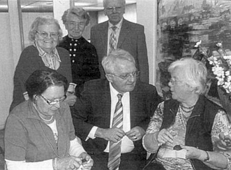 Emmi Schlägerová (vzadu uprostřed) při setkání s viceprezidentem Evropského parlamentu Rainerem Wielandem (vpředu uprostřed), který si nechává vysvětlit techniku škrábání šumavských velikonočních kraslic