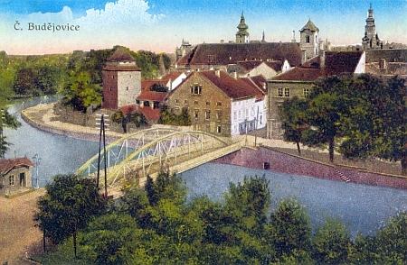 Stará pohlednice Budějovic, kde most přes Malši dosud střeží strážní domek někdejší koněspřežky