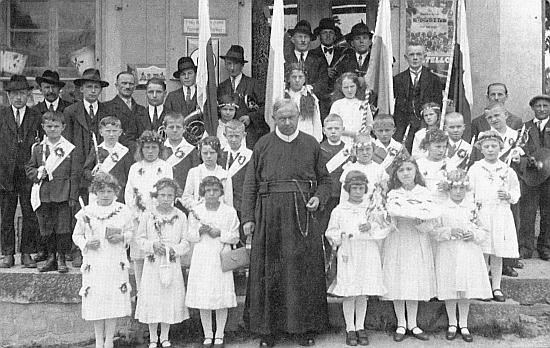 První svaté přijímání v Cetvinách 1936. deset let před odsunem - děti s panem farářem stojí při vstupních schodech téhož domu, který vidíme na následující pohlednici hned nalevo od kostela Narození Panny Marie