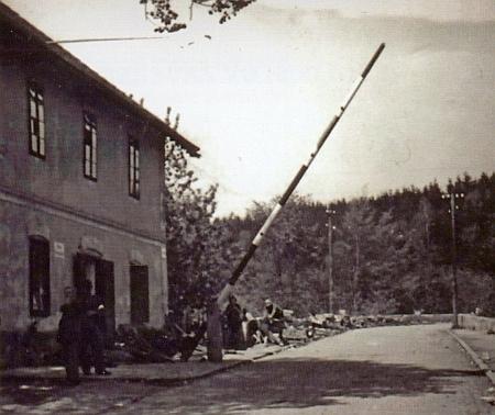"""Ulice Pod Kamenem čp. 179, lokalita zvaná U Trojice, kde byla hranice mezi """"Říší"""" a Protektorátem Čechy a Morava, dvě celnice a závora, u níž stojí v roce 1945 americký voják"""