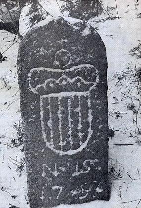 Zasněžený schwarzenberský hraniční kámen uMalče na Prachaticku...