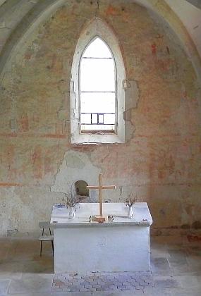 Oltářní menza a středověké nástěnné malby navýchodní straně kněžiště s lomeným oknem