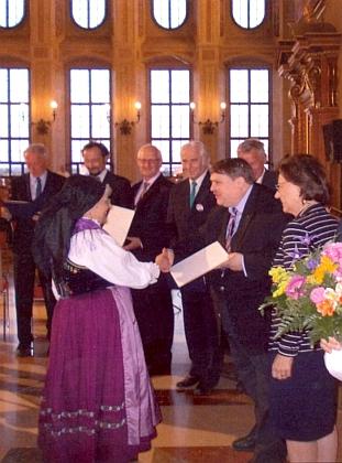 Z rukou Bernda Posselta přijímá u příležitosti Sudetoněmeckého sněmu v Augsburgu roku 2014 cenu za uchování národopisného dědictví - za ní vidíme laureáta ceny za hudbu Tomáše Spurného, vedoucího kapely Pošumavská dudácká muzika