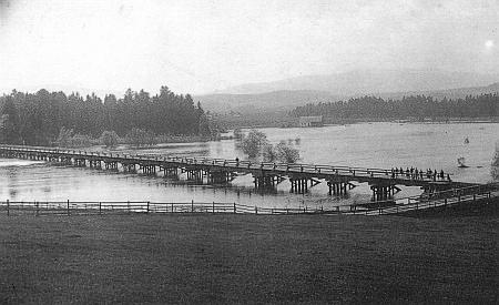 Dlouhý dřevěný most mezi dnes zatopenými obcemi Radslav a Dolní Borková na mladé Vltavě a staré pohlednici