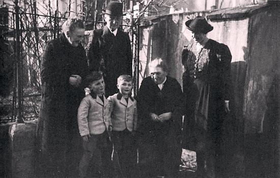"""Adalbert Leppa, otec bratří Karla Franze a Konrada Leppových a také kmotr Constanze Sedlmeyerové, je tu na snímku, pořízeném někdy v roce 1938, zachycen se svou ženou Marií, roz. Sedlmeyerovou, její sestrou Elise a rovněž s dvojčaty Axelem a Ivo Sedlmeyerovými a jejich matkou Constanze, roz. Kolaczekovou - poválečný osud svého otce, matky a tety popsal Karl Franz Leppa v povídce """"Die Fahrt mit dem Tod"""", tj. """"Výprava se smrtí"""": otec zemřel roku 1945 na selském povoze těsně před rakouskou hranicí, matka skonala už v německém vyhnanství sedm let poté v roce 1952, tetu zastihla smrt tři dny po té otcově už v bavorských Frankách, pohřbeni však jsou oba ještě v rakouském Mühlviertelu"""