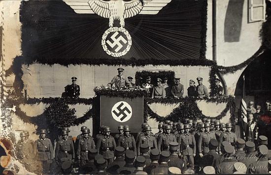 """""""Viděli jsme přece, že Hitler vede německý národ do války..."""" na dvou přesvědčivých záběrech """"Vůdcova"""" pobytu v Krumlově 20. října roku 1938 cestou vystlanou květy na tribunu a při jeho projevu"""