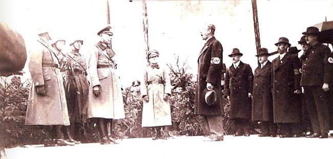 S páskou na rukávě tu předává Železnou Rudu německé armádě - úřad starosty přitom už nezastával, starosta Ignaz Brandl stojí za ním