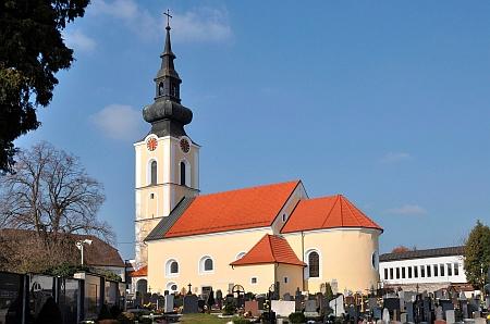 Farní kostel sv. Michaela v Leondingu s výrazným křížem na vrcholu věže a hřbitovem kolem