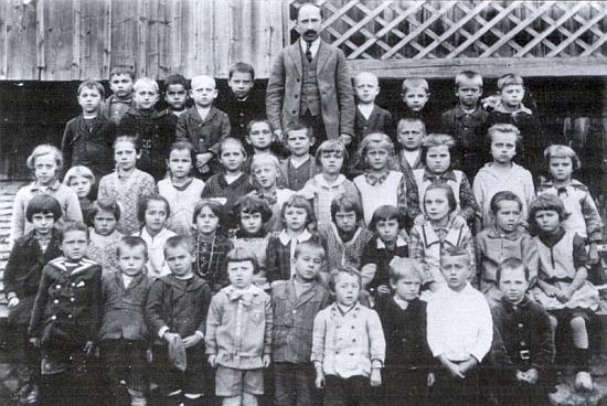 Snímek školní budovy ve Vlčích Jamách a žáků zdejší dvojtřídky ročníků narození 1920-23 s panem učitelem Josefem Wernerem, o němž pojednává i přilehlý Spannbauerův text v krajanském měsíčníku