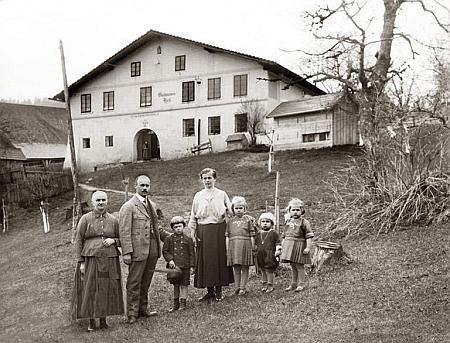 Mohutné selské stavení v zaniklé Havránce (Rabenhütte)     a rodina Aloise Pangerla před ním na snímku z roku 1923