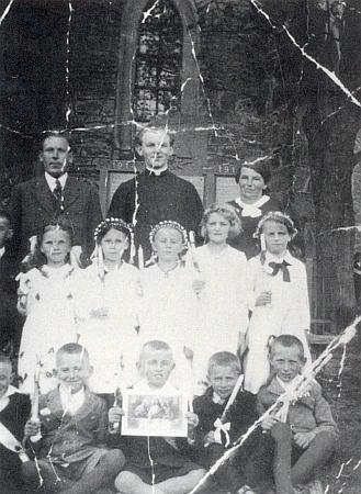 Děti ze Scheureku s panem učitelem Emilem Spitzenbergerem, farářem Wenzlem Schmidtem aučitelkou ručních prací zachytil      tento polámaný snímek při prvním svatém přijímání u památníku padlých při zdi někdejšího kostela v Knížecích Pláních