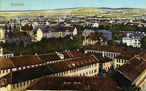 """Tato pohlednice zachycuje továrnu z druhé strany: v popředí je továrna L.&C. Hardtmuth, za ní Lamezanova a Hardtmuthova vila av další """"řadě"""" pak zleva synagoga, okresní zastupitelstvo a Stegmannova továrna (dnes jsou tyto budovy spojeny)"""