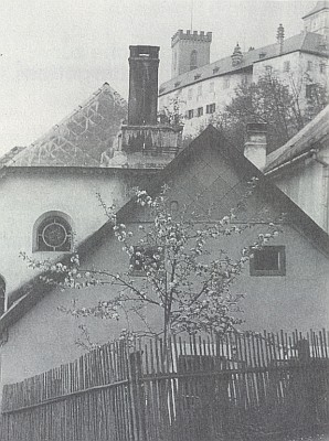 """Snímek zachycuje hrad v Rožmberku s čelní fasádou synagogy a komínem v její střeše pod sebou, vepředu tzv. """"Judenteilhaus"""" Benedikta Radlera"""