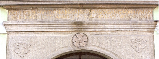 Detail německého nápisu s letopočtem 1954 na renesančním portálu radnice v Benešově nad Černou - vlys ve tvaru pětilisté růže upomínal na Rožmberky, kteří byli benešovskou vrchností v letech 1387-1611, štítky GW se vztahovaly k osobě Hanse Weningera, benešovského měšťana, který se pravděpodobně podílel na stavbě radnice  a správě města