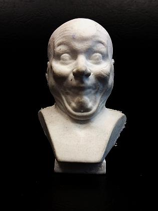 """Jedna z hlav jako suvenýr z vídeňského Belvederu v podobě mazací pryže (originál z alabastru      nese název """"Ein absichtlicher Schalksknarr"""", tj. """"úmyslný šašek"""")"""
