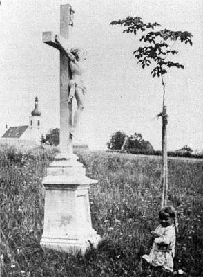 """Tzv. """"Moarkreuz"""" v Dolní Vltavici, v pozadí kostel sv. Linharta a lípa u fary, z níž vyhlíží jen střecha"""
