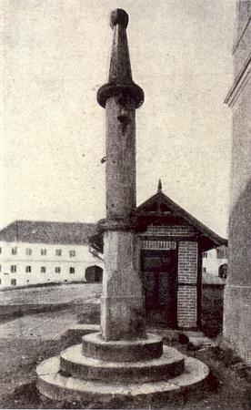 Kamenný pranýř se zvonkem na někdejší dolnovltavické návsi zachycuje snímek údajně z doby před rokem 1921