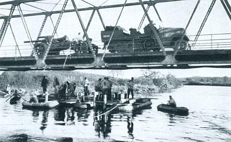 A ještě jeden záběr dolnovltavického mostu z října 1938, kdy ho za dohledu vojáků wehrmachtu na člunech přejíždí těžké dělostřelectvo