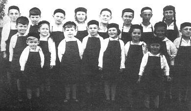 """S dětským pěveckým sborem tiskařské firmy Steinbrener zvaným """"Setzerbuben"""" (v zadní řadě druhý zleva)"""