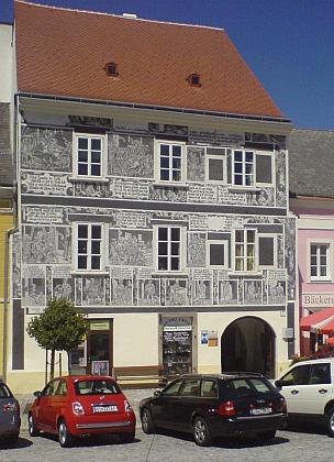 Náměstí ve Weitře s pomníkem padlých z obou světových válek, svatotrojickým sloupem a domem ze 16. století se sgrafity,...