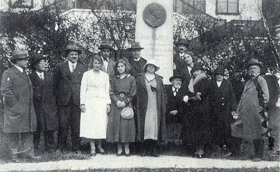 Zde je Taschek roku 1933 zachycen sedící při hořickém památníku, zobrazujícím na bronzovém reliéfu jeho vlastní podobu, jedna z mladých dívek stojících v popředí je pak Anna Mugrauerová, poslední představitelka Marie vmeziválečných insenacích pašijových her, jejichž budova se zvedá za skupinou na snímku