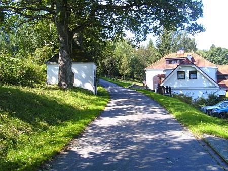 Bývalá Tobischova myslivna ve Frýdavě a kaplička naproti mezi vzrostlými stromy na jeho snímcích