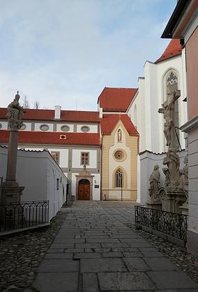 Stará kolorovaná pohlednice zachycuje část někdejšího dominikánského konventu, kde českobudějovická piaristická kolej sídlila a stejný pohled v roce 2021