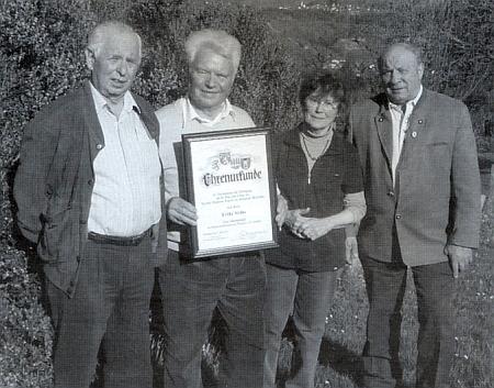 Se svou ženou, Karlem Swihotou (prvý zleva) a Rudolfem Paulikem, v rukou má čestnou listinu za práci pro Neumannovu kapli na Třístoličníku