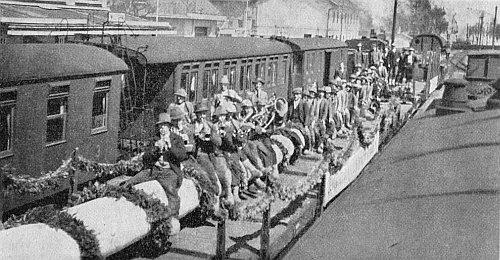 Scéna z nádraží ve Volarech: Dřevorubci ze Zátoně sedí obkročmo na jedli z Boubína a muzicírují k tomu