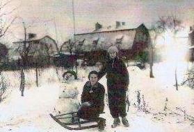 Inge sedící na sáňkách, vedle ní stojí sestra Eva