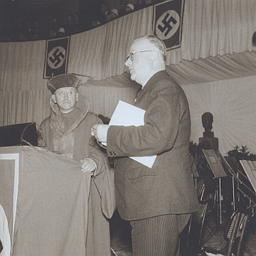 Watzlik tu 16. června roku 1939 přijímá ve slavnostním sále Německého domu na pražských Příkopech gratulaci Konrada Henleina k udělení Eichendorffovy ceny (za Henleinem stojí zpola zakryt K. H. Frank, vlevo přihlíží vúboru rektora německé univerzity v Praze význačný pedagog Dr. Ernst Otto, který cenu zřejmě předával