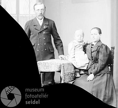 Rozbitá skleněná deska ze Seidelova fotoateliéru z 29. května 1921, psaná na přeškrtnuté jméno Josef a adresu Josef Wick, Irresdorf 19, zachycuje Josefa Wicka s manželkou Theresií a dvouletou dcerou Marií