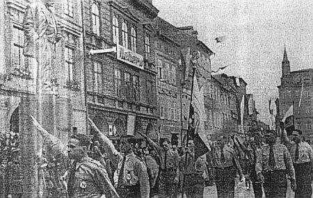 """I Češi měli svůj fašismus: tady zdraví """"šedé košile"""" na českobudějovickém náměstí ještě     """"za republiky"""" árijským pozdravem sochu Zátkovu před radnicí (socha dnes stojí na jejím dvoře)"""