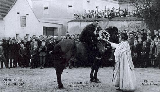 Děkan Winter předává posvěcený kříž předjezdci velikonoční jízdy v roce 1936 - v pozadí fara ve Strýčicích