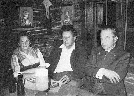 """Se svým manželem a  a vedle něho sedícím spisovatelem Dr. Leo Hansem Mallym (vpravo) v """"božím koutě"""" selské jizby skansenu v Lindbergu"""