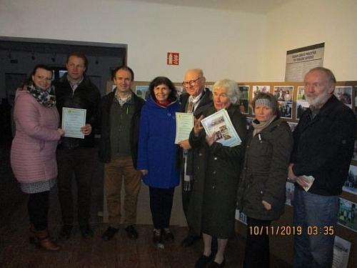 Stojí uprostřed při udělení ceny Slunce a svoboda v roce 2019 od česko-rakouského protijaderného sdružení, , vpravo od něj je Mathilde Halla, třetí zleva stojí Bernard Riepl