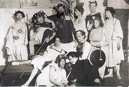 """""""Antická slavnost"""" ze dne 22. února roku 1903 v mnichovském bytě Hanny a Karla Wolfskehlových zachycená snímkem, na němž uprostřed trůní sedící básník Stefan George a v horní řadě za ním stojí uprostřed vousatý Karl Wolfskehl jako Dionýsos"""
