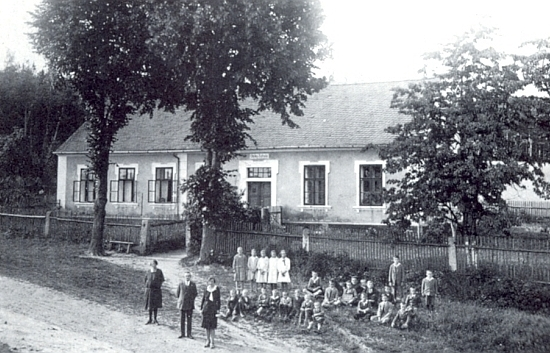 Na snímku z roku 1931 je zachycen před školou v Mirkovicích s 26 žáky, svou paní a zcela vlevo stojící učitelkou ručních prací Annou Schneiderovou z Mělnice (Melnitz)