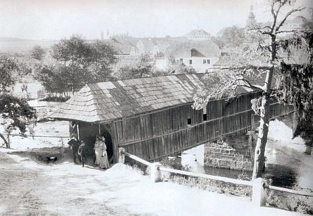 Krytý dřevěný most ve Svojšíně na snímku někdy z roku 1908 - v roce 1931 byl stržen a nahrazen současným betonovým