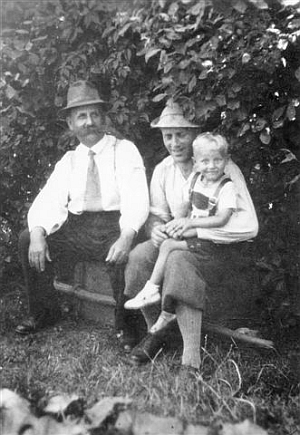 Herwig Zahorka na klíně svého otce Franze Zahorky mladšího roku 1935 v Hodějovicích, kde byl vedle nich sedící dědeček Franz Zahorka starší v letech 1920-1936 řídícím školy a zasloužil se svou žádostí< o elektrifikaci obce v roce 1932