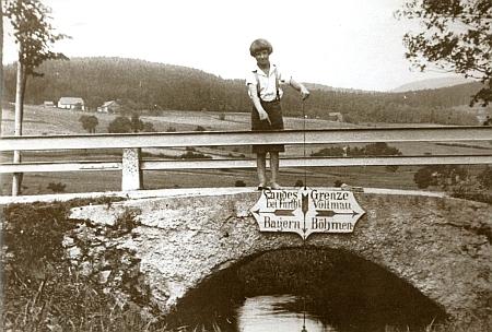 Snímek z doby kolem roku 1920 s hraničním mostkem a ukazateli na něm